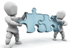 Clipart Illustration of Two White Characters Holding Blue Jigsaw Puzzle Pieces And Fitting Them Together